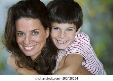 Happy mother and son smiling outdoors