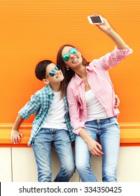 Happy mother and son teenager taking picture self portrait on smartphone in city, over colorful background, wearing a checkered shirt and sunglasses
