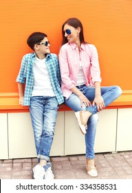 Happy mother and son teenager wearing a checkered shirt and sunglasses having fun in city
