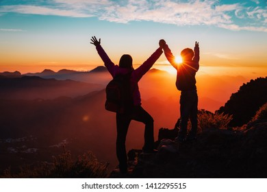 happy mother and son travel in mountains at sunset