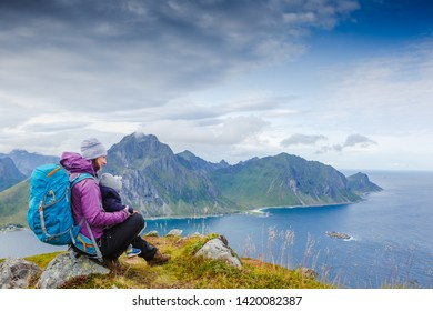 Happy mother and son travel together and anjoying the view. Lofotes, norway. Family trip in the mountains, vacation with infant