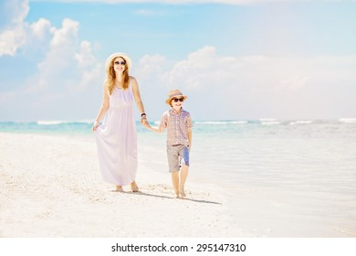 Happy mother and son walk along the white sand ocean beach having great family time on vacation on Pandawa Beach, Bali. Paradise, travel, vacation concept