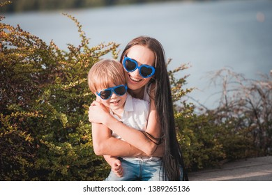 Happy mother with son in white t-shirt wearing glasses smiling outdoor