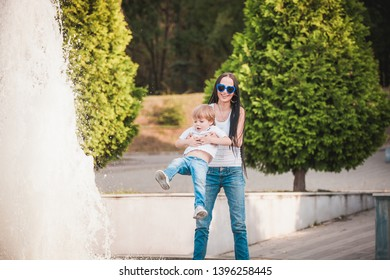 Happy mother with son in white t-shirt wearing glasses near fountain in park outdoor