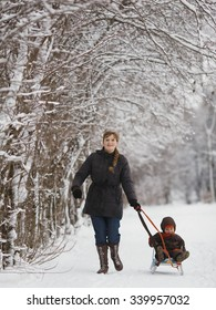 happy mother with son in winter park with sled