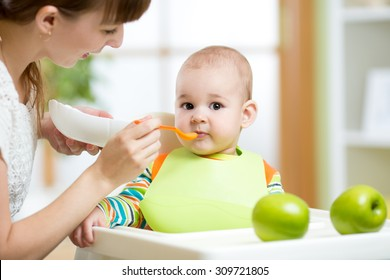 Happy mother spoon feeding her baby boy