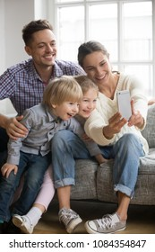 Happy mother taking family selfie with husband and kids looking at smartphone, playful adopted children siblings having fun posing for funny photo on phone with smiling mom and dad together, vertical