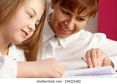 Happy mother teaching her cute daughter
