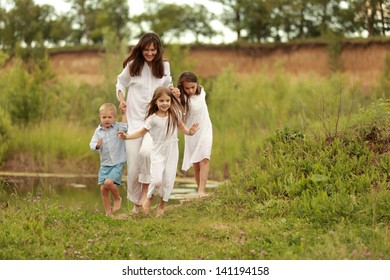 Happy mother with three children walking in a field in spring time