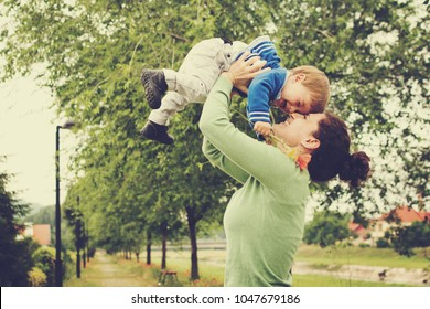 Happy mother and toddler son outdoors in spring playing together. Mom lifting a child up. Matte greenish filter.