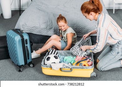 happy mother trying to pack clothes into suitcase while daughter sitting in it