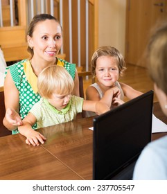 Happy mother with two children glad hearing words of social worker at home