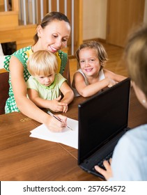Happy mother with two children glad hearing words of social worker at home. Focus on woman
