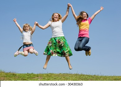 Happy Mother and two daughter jumping on green meadow
