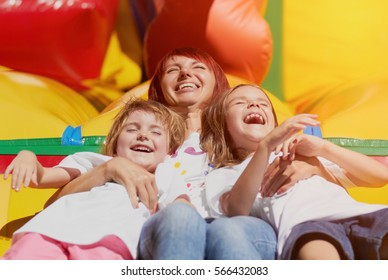 Happy mother & two daughters laughing out loud,playing on inflatable bouncing castle outdoor in bright summer day.Friendship,unity,love concept.Mom&cute little girls having fun on playground outdoor