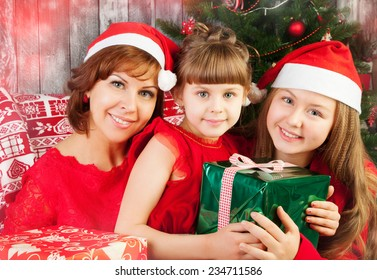 Happy mother with two daughters in santa claus hats during Christmas time