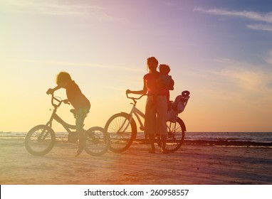 happy mother with two kids biking at sunset