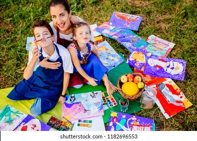 Happy mother, and two kids are painting in the park. The concept of a happy family.