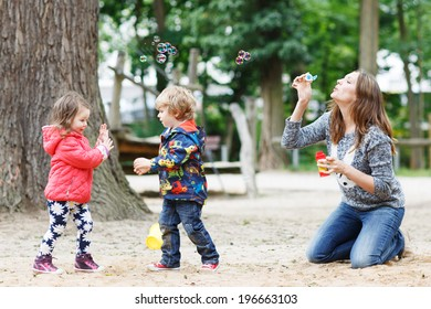 Happy mother and two little children playing together with soap bubbles on playground in summer