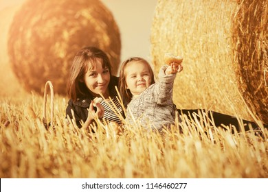 Happy mother and two year old girl relaxing next to hay bales in summer harvested field