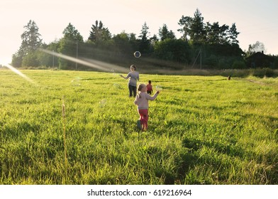 Happy mother walking with children and blowing soap bubbles in the evening sun rays