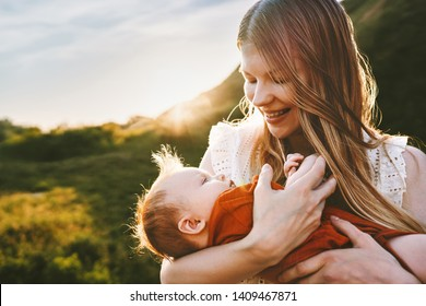 Happy mother walking with infant baby outdoor family lifestyle mom holding child maternity Mothers day summer travel vacations
