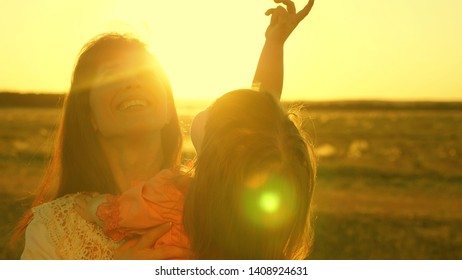 happy mother walks with her daughter in her arms in the rays of the sunset. Mom is talking with happy baby, baby is sitting on mother's arms at sunset of golden sun. Slow motion.