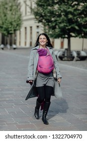 Happy mother wearing her baby in woven wrap. Trendy woman carrying her little child in sling and going for walk on sunny day.