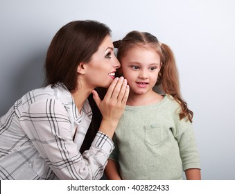 Happy mother whispering the secret to her cute kid girl in ear with fun face on blue background