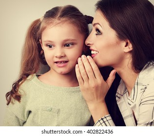 Happy mother whispering the secret to her cute kid girl in ear with fun face. Vintage close portrait