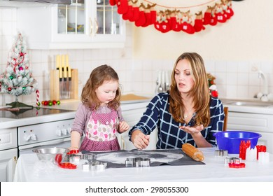 Happy mother, young woman in red santa hat baking christmas cookies together with her little daughter, cute blonde kid girl, sitting at the table in domestic kitchen