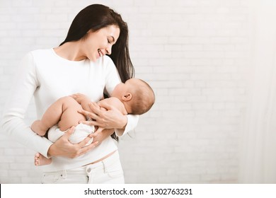 Happy motherhood. Mother nursing her baby, smiling and singing lullaby, copy space