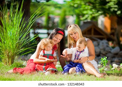 Happy mothers with children playing outdoors in spring park