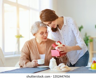 Happy mother's day! adult daughter gives gift and congratulates an elderly mother on the holiday