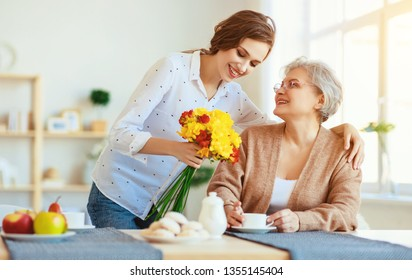 Happy mother's day! adult daughter gives flowers and congratulates an elderly mother on the holiday