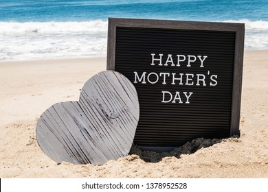 Happy Mother's day background with black board and heart on the sandy beach near the ocean.