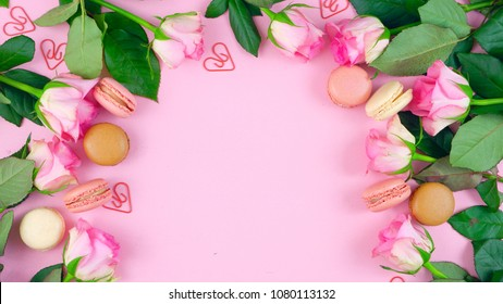 Happy Mother's Day background of pink roses and macaron cookies on pink wood table.