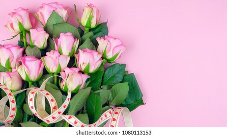 Happy Mother's Day background of pink roses with copyspace on pink wood table.