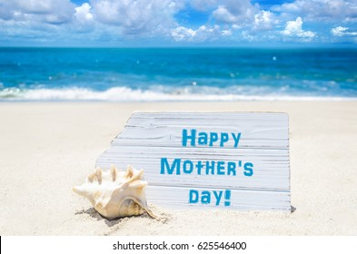 Happy mother's day background with seashell on the sandy beach near the ocean