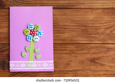 Happy Mother's day or birthday greeting card with flower isolated on a wood background with empty place for text. Card made with the use of wooden buttons, lace, paper, plastic leaves, glue, scissors