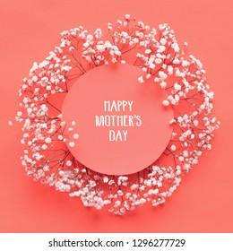 Happy Mothers Day Card. Flat lay greeting card with beautiful little white flowers on living coral pantone color paper background.