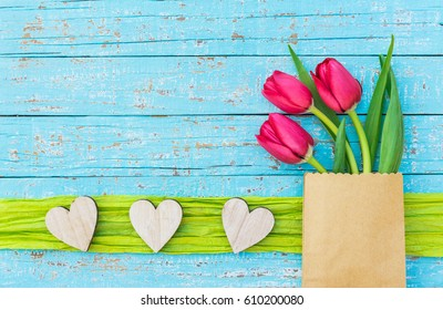 Happy Mother's Day card with fresh pink tulips flowers and hearts on blue wooden background.
