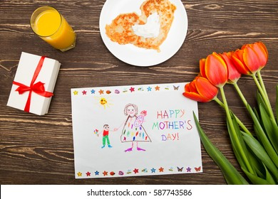 Happy mothers day card made by a child. Mother's hands hold a card a gift from the child and a coffee cup on a wooden background of a table.