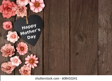 Happy Mothers Day chalkboard heart with rustic paper flower side border over a wood background