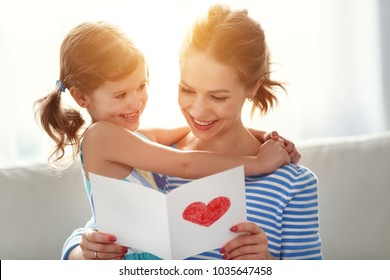 Happy mother's day! Child daughter congratulates moms and gives her a postcard
