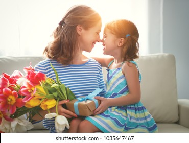 happy mother's day! child daughter congratulates mother and gives a bouquet of flowers to tulips and gift