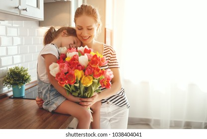 happy mother's day! child daughter congratulates mother and gives a bouquet of flowers to tulips