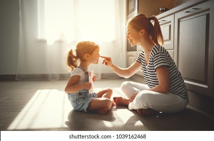 happy mother's day! child daughter congratulates her mother and on  floor in kitchen read postcard