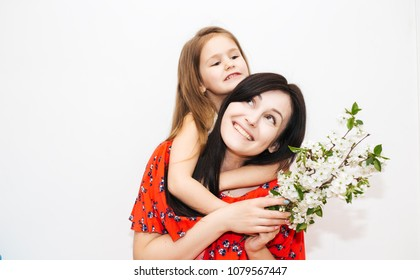 Happy mother's day! Child daughter congratulates mom and gives her flowers . Portrait of Mum and girl smiling and hugging. Family holiday and togetherness.
