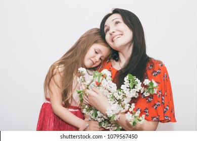 Happy mother's day! Child daughter congratulates mom and gives her flowers indoor on white . Mum and girl smiling and hugging. Family holiday and togetherness.